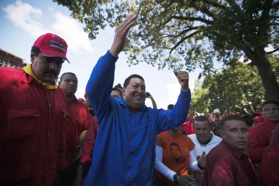 Venezuela's President Hugo Chavez waves to supporters during a stop of a campaign caravan in Sabaneta, Venezuela, Monday, Oct. 1, 2012. Venezuela's presidential election is scheduled for Oct. 7. At left Venezuela's Foreign Affairs Minister Nicolas Maduro.(AP Photo/Rodrigo Abd)