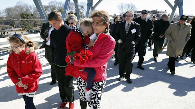 Raeann Melvin, center, of Harker Heights, Tex., walks with her daughters Cassidy, 9, left, and Cailey, 5, on the way to a wreath ceremony to mark the 50th anniversary of the sinking of the USS Thresher, Saturday, April 6, 2013. in Portsmouth, N.H. Melvin's father was one of the 129 men who died when the submarine went down. (AP Photo/Michael Dwyer)