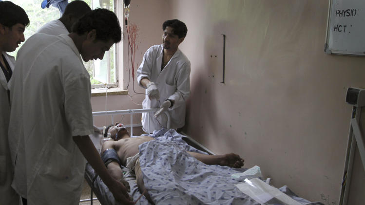 A wounded Afghan laborer undergoes treatment at the hospital in Kandahar south of Kabul, Afghanistan on Tuesday, May 24, 2011. A roadside bomb killed 10 laborers and wounded 28 on Tuesday as they were being driven to work to clean streams in southern Afghanistan, officials said. (AP Photo/Allauddin Khan)