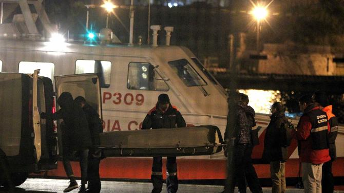 Italian Coast Guard members carry a body as they arrive in the Brindisi harbour
