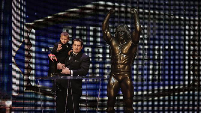 "IMAGE DISTRIBUTED FOR WWE - Steve Michalek, father of the late Connor ""The Crusher"" Michalek, 8, holds his son Jackson, as he accepts the Ultimate Warrior Award in honor of Connor at the WWE Hall of Fame Ceremony, on Saturday, March 28, 2015 in San Jose, Calif. Michalek passed from brain cancer in 2014. (Don Feria/AP Images for WWE)"