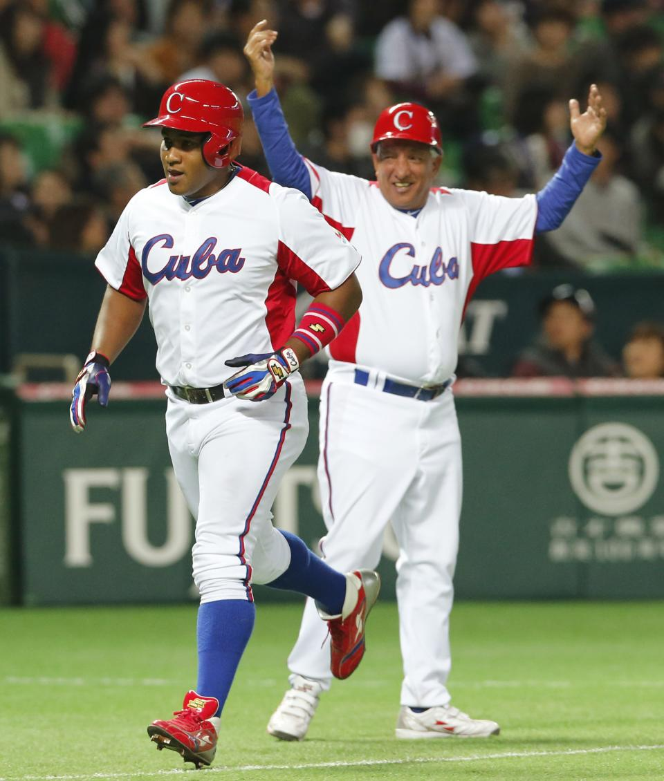 Cuba's leftfielder Alfredo Despaigne rounds third base past coach Primitivo Diaz after hitting a three-run homer off Japan's pitcher Takeru Imamura in the eighth inning of their World Baseball Classic first round game in Fukuoka, Japan, Wednesday, March 6, 2013. (AP Photo/Koji Sasahara)