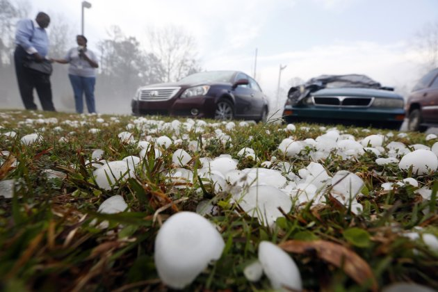 Golfball sized hail litter the ground by  Andrew Stamps and his wife Valorie as they prepare to cover their shattered rear window of her 2009 Toyota Avalon in Pearl, Miss., Monday, March 18, 2013, fol