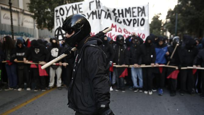 Black-clad protesters march during an anniversary rally marking the shooting of a 15-year-old student by a policeman in 2008, in Athens