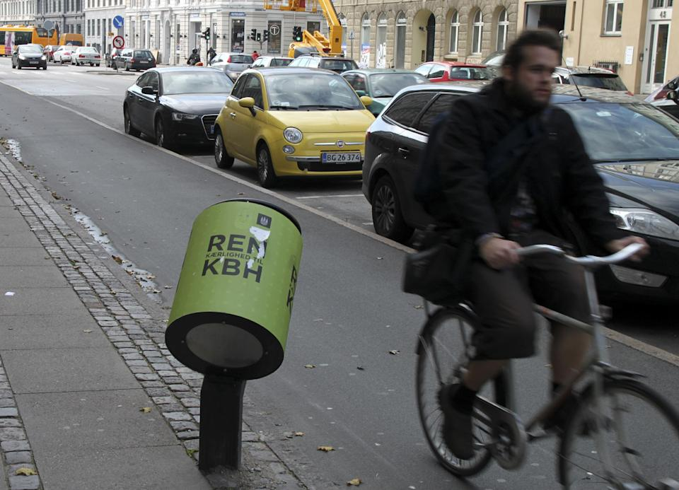 A man rides past a tilted trash bin in Copenhagen on Oct. 3, 2012. The photo is not from the route labeled a superhighway, but a downtown Copenhagen street with the same kind of bicycle-friendly features.  (AP Photo/Jan M. Olsen)