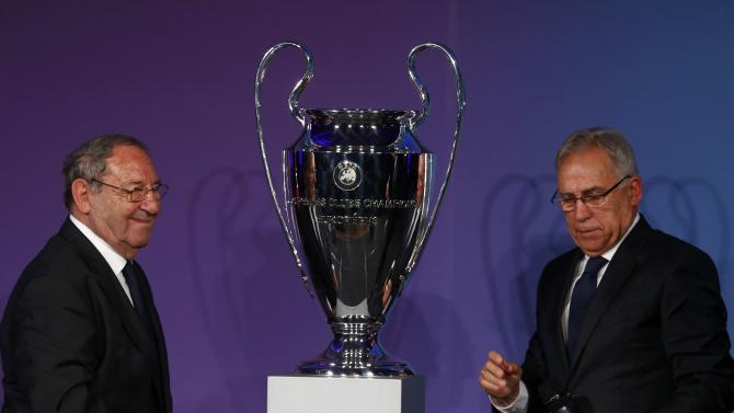 Former Spanish soccer players Gento and Amancio Amaro Varela stand around the Champions League trophy during the official handover ceremony in Berlin