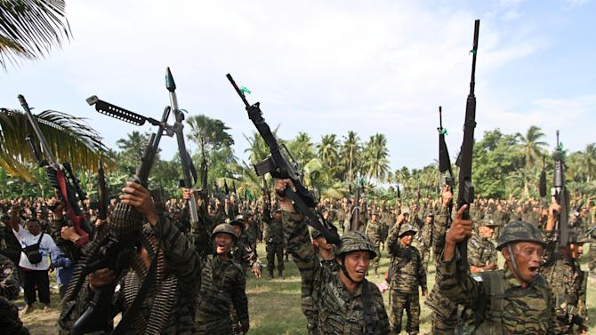 "Members of the Moro Islamic Liberation Front shout ""Allahu Akhbar,"" or God is great, as they gather at their stronghold at Camp Darapanan in Maguindanao province in southern Philippines to coincide with the tentative peace-signing agreement between MILF and the Government at Malacanang Palace in Manila, Philippines, Monday, Oct. 15, 2012. (AP Photo/Karlos Manlupig)"