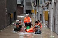 Rescuers evacuatw an elderly woman from her flooded home in Chongqing, in southwest China, on July 23. Beijing authorities have reportedly ordered Chinese media to stick to positive news about record weekend floods, after the death of at least 37 people sparked fierce criticism of the government