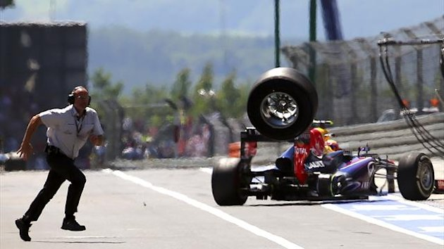 An unidentified FIA official runs over to the pits as a lost rear tyre of Red Bull Formula One driver Mark Webber of Australia bounces through the pit lane during the German F1 Grand Prix at the Nuerburgring circuit (Reuters)