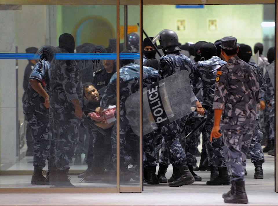 Kuwait's riot police arrest a man during a demonstration in Kuwait City in the early hours of Monday, Oct. 22, 2012. Several thousand protestors from opposition groups, local tribes and former MPs gathered in different points of Kuwait City to demonstrate against the Government's amendment of the country electoral law.(AP Photo/Gustavo Ferrari)