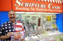 Scripture Candy founder Brian Adkins poses at his booth at the Sweet and Snack Expo