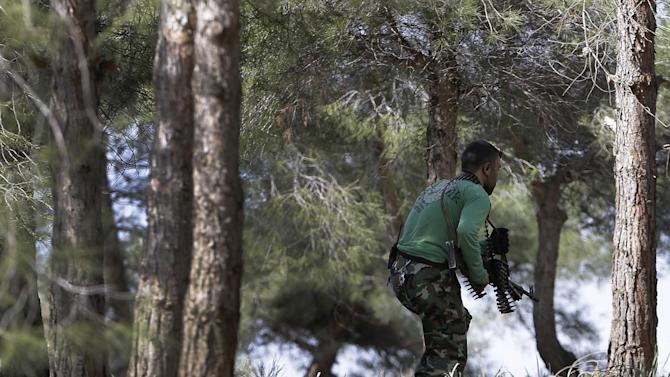 A Free Syrian Army fighter from the Knights of the North brigade moves to reconnaissance a Syrian army forces base of al-Karmid, at Jabal al-Zaweya, in Idlib province, Syria, Wednesday, Feb. 27, 2013. Syrian warplanes carried out airstrikes on rebels trying to storm a police academy outside Aleppo on Wednesday, while jihadi fighters battled government troops along a key supply road leading to the southeastern part of the city, activists said. (AP Photo/Hussein Malla)