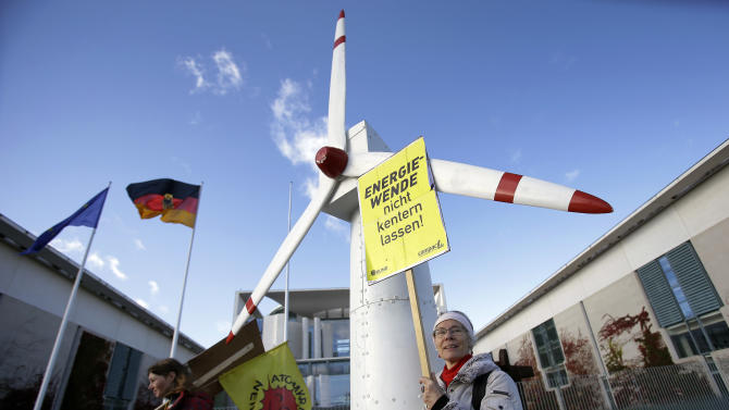Protesters hold a placard and flag next to a model of a wind turbine, during a demonstration to support the change of energy supply in front of the chancellery in Berlin, Germany, Friday, Nov. 2, 2012. Poster reads : 'Don't let the energy-change capsize'.  On Friday,  German Chancellor Angela Merkel held a meeting with the country's 16 state governors to coordinate the country's energy transition from nuclear to renewable power sources within a decade (AP Photo/Michael Sohn)
