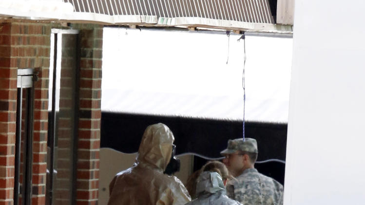Federal authorities, some in hazmat suits search at a small retail space where neighboring business owners said Everett Dutschke used to operate a martial arts studio. Wednesday, April 24, 2013 in Tupelo, Miss., in connection with the recent ricin attacks. No charges have been filed against Dutschke and he hasn't been arrested. (AP Photo/Rogelio V. Solis)