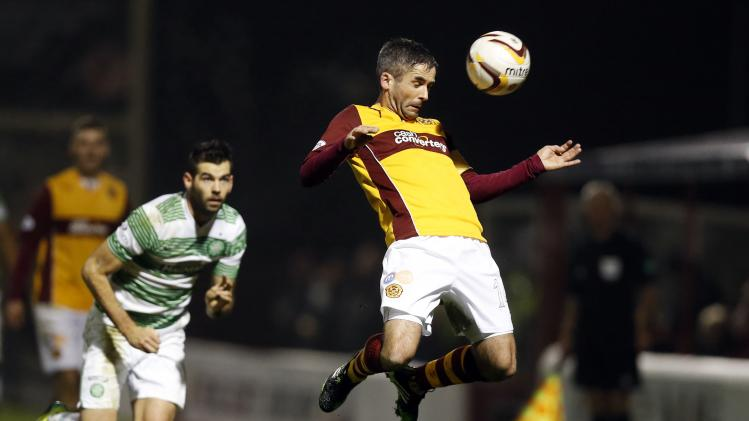 Celtic's Joe Ledley looks on as Motherwell's Keith Lasley jumps for the ball during their Scottish Premier League soccer match at Fir Park Stadium in Motherwell