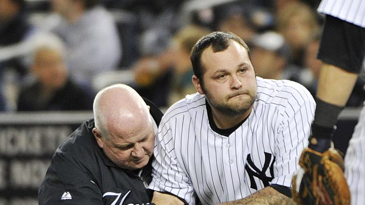 A trainer, left, helps New York Yankees relief pitcher Joba Chamberlain who was hit by a broken bat when Baltimore Orioles' Matt Wieters hit a single during the twelfth inning of Game 4 of the American League division baseball series on Thursday, Oct. 11, 2012, in New York. (AP Photo/Bill Kostroun)