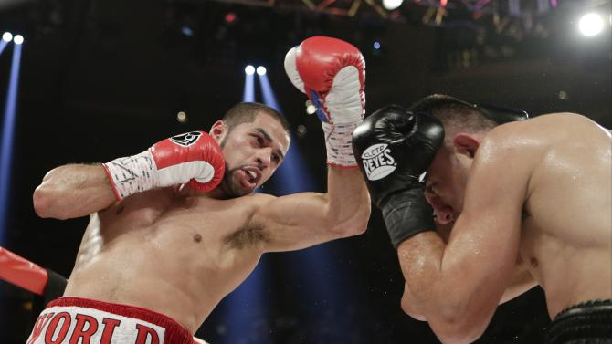 Sadam Ali, left, punches Francisco Santana during the fifth round of a boxing bout Saturday, April 25, 2015, at Madison Square Garden in New York. Ali won the fight. (AP Photo/Frank Franklin II)