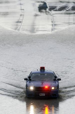 A state trooper drives through the water in the eastbound lanes of Interstate 94, near the Lodge exit lanes Tuesday, Aug. 26, 2014 near Detroit following a thunderstorm that past through Southeast Michigan. The National Weather Service says winds reaching 60 mph in Wayne County's Canton Township near Detroit and in Washtenaw County's Pittsfield Township near Ann Arbor. It says a 2-foot-diameter tree fell in Redford, near Detroit. (AP Photo/Detroit News, Steve Perez)