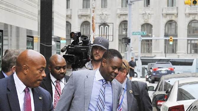 Detroit Emergency Financial Manager Kevyn Orr, center, followed by the media, leaves U.S. District Court in Detroit, Wednesday, Oct. 1, 2014. Orr is expected to testify Wednesday afternoon and again Thursday in the city's federal bankruptcy trial (AP Photo/Detroit News, Daniel Mears)  DETROIT FREE PRESS OUT; HUFFINGTON POST OUT; MANDATORY CREDIT