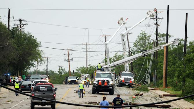 Crews work to clear power lines damaged by Wednesday's tornado in Cleburne, Texas on Thursday, May 16, 2013. Ten tornadoes touched down in several small communities in Texas overnight, leaving at least six people dead, dozens injured and hundreds homeless. Emergency responders were still searching for missing people Thursday afternoon. (AP Photo/Ron Russek II)