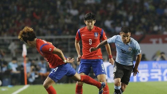Uruguay's Maximiliano Pereira, right, fights for the ball against South Korea's Son Heung-min and Kim Young-gwon, left, during their friendly soccer match at Goyang Stadium in Goyang, South Korea, Monday, Sept. 8, 2014. Uruguay defeated South Korea 1-0