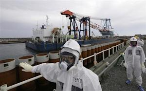 TEPCO employees stand next to an impervious wall made of steel pipe sheet pile installed along the coast in Fukushima