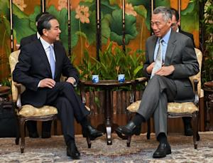 Chinese Foreign Minister Wang Yi (L) talks with Singaporean …