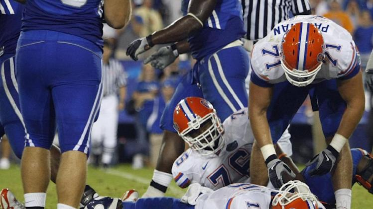 In this Sept. 26, 2009, file photo, Florida Matt Patchan (71) and Marcus Gilbert (76) look on as Florida quarterback Tim Tebow lies on the turf after being sacked during an NCAA college football game against Kentucky in Lexington, Ky. Tebow received a concussion on the play that put him in the hospital for a night. The parties in a class-action head injury lawsuit against the NCAA that deals with concussion issues announced a settlement in a filing in federal court in Chicago on Tuesday, July 29, 2014