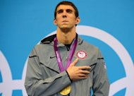 Gold medalist US swimmer Michael Phelps listens to his national anthem on the podium after winning the men's 200m individual medley swimming event at the London 2012 Olympic Games in London