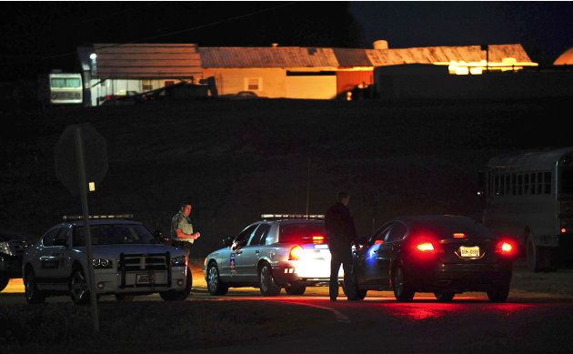 Law enforcement personnel work a check point Wednesday, Jan. 30, 2013, in Midland City, Ala, below the home where Tuesday's school bus shooting suspect is barricaded in a bunker with a young child as 