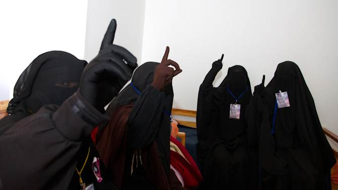 """FILE  - In this Jan.18, 2012 file photo, the four ultraconservative hunger striking women students of the Manouba Arts and Humanities raise one finger to mean """"There is only one god"""" in an apartment outside the university, near Tunis, as classes and exams at Manouba University's humanities department have been put on hold by a sit-in demanding students be allowed to attend class in the conservative face veil, known as the Niqab. (AP Photo/Amine Landoulsi, File)"""