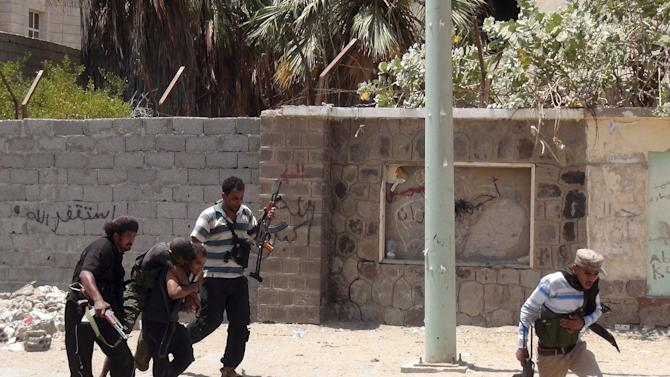 Fighters loyal to Yemen's President Hadi carry a comrade who sustained injuries during clashes with Houthi fighters in Aden