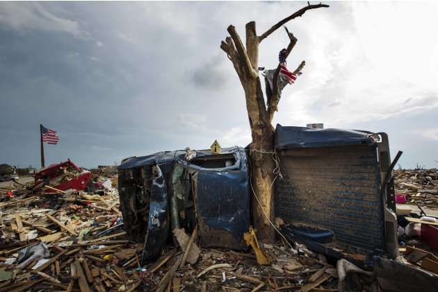 The body of a pickup truck is wrapped around a tree trunk after being thrown there by by a tornado in Moore, Oklahoma
