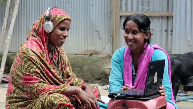 """In this Sept. 30, 2012, photo, Bangladeshi Info Lady Mehedi Akthar Misty, right, helps Amina Begum, 45, to talk with her husband with Skype at Jharabarsha, in a remote impoverished farming village in Gaibandha district, 120 miles (192 kilometers) north of capital Dhaka, Bangladesh. Begum had never seen a computer until a few years ago, but now she's on Skype regularly with her husband. A woman on a bicycle brings the Internet to her. Dozens of """"Info Ladies"""" bike into remote Bangladeshi villages with laptops and Internet connections, helping tens of thousands of people - especially women - get everything from government services to chats with distant loved ones. (AP Photo/A.M. Ahad)"""