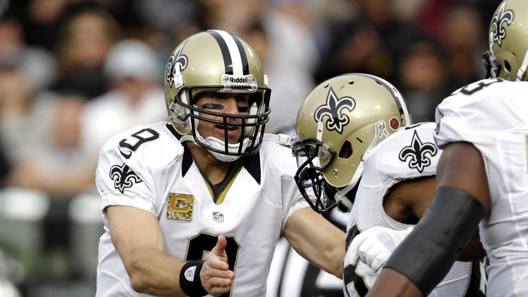 New Orleans Saints quarterback Drew Brees, left, greets running back Mark Ingram after he scored a touchdown on a 27-yard run during the third quarter of an NFL football game against the Oakland Raiders in Oakland, Calif., Sunday, Nov. 18, 2012. (AP Photo/Marcio Jose Sanchez)