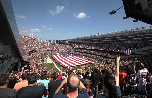 Fan cheer during the national anthem as a giant United States flag is held over Soldier Field on the 10th anniversary of the Sept. 11 attacks before an NFL football game between the Chicago Bears and