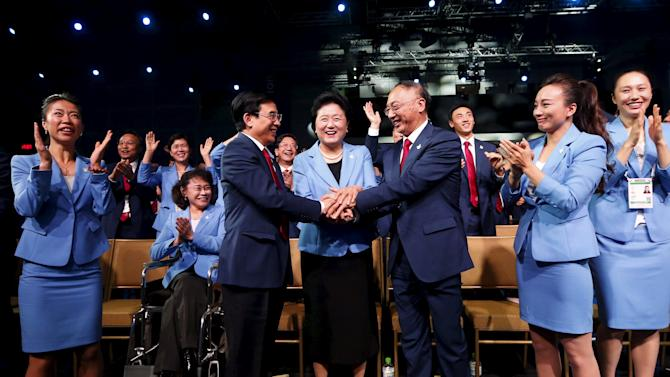 Members from Beijing 2022 delegation celebrate after Beijing was awarded the 2022 Winter Olympic Games, defeating Almaty in the final round of voting, during the 128th IOC session in Kuala Lumpur