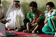 Iraqi Paralympian Ahmed Naas sits with his family at their home in Batha. Naas recalled how his relatives and friends in Batha greeted him with three days of celebrations, with people from around the town visiting to congratulate him