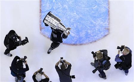 Los Angeles Kings' Jarret Stoll is pursued by photographers as he holds up the Stanley Cup after his team defeated the New Jersey Devils in Game 6 of the NHL Stanley Cup hockey final in Los Angeles