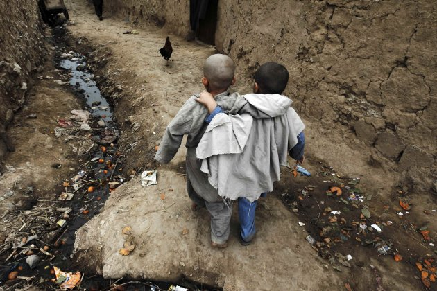 Boys walk down an alley at a slum on the outskirts of Islamabad