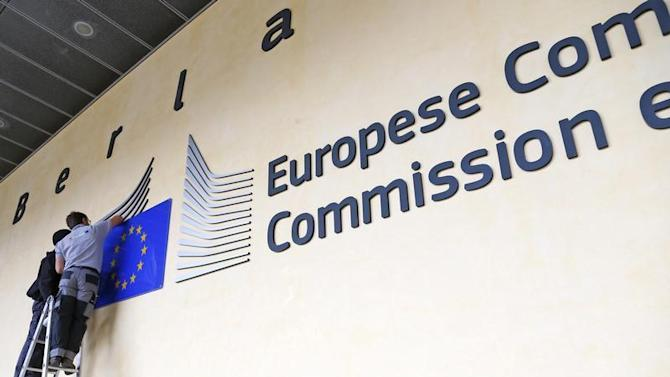 Workers adjust and clean the logo of the European Commission at the entrance of the EC headquarters in Brussels