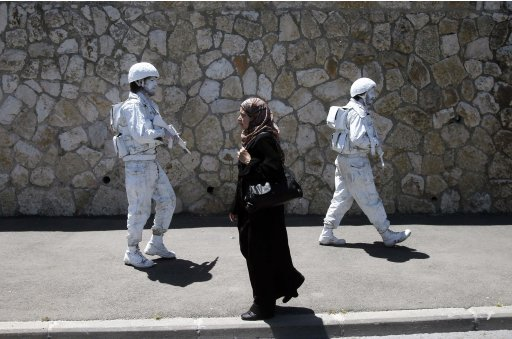 A woman walks past Israeli artists, one of them Yuda Braun, in Jerusalem