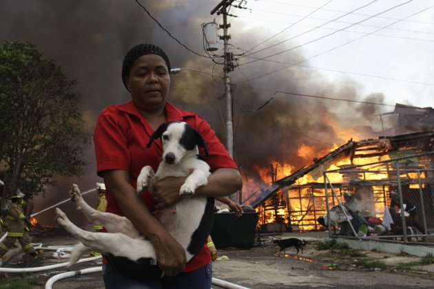 A woman carries a dog as a fire blazes in the background at El Chorrillo neighborhood in Panama City