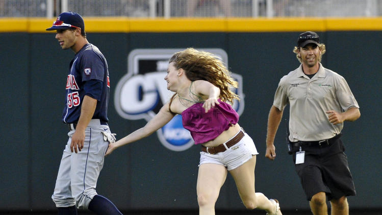 An unidentified spectator rushes the playing field and pats Arizona center fielder Joey Rickard in the seventh inning of Game 2 of the NCAA College World Series baseball finals against South Carolina in Omaha, Neb., Monday, June 25, 2012. (AP Photo/Eric Francis)