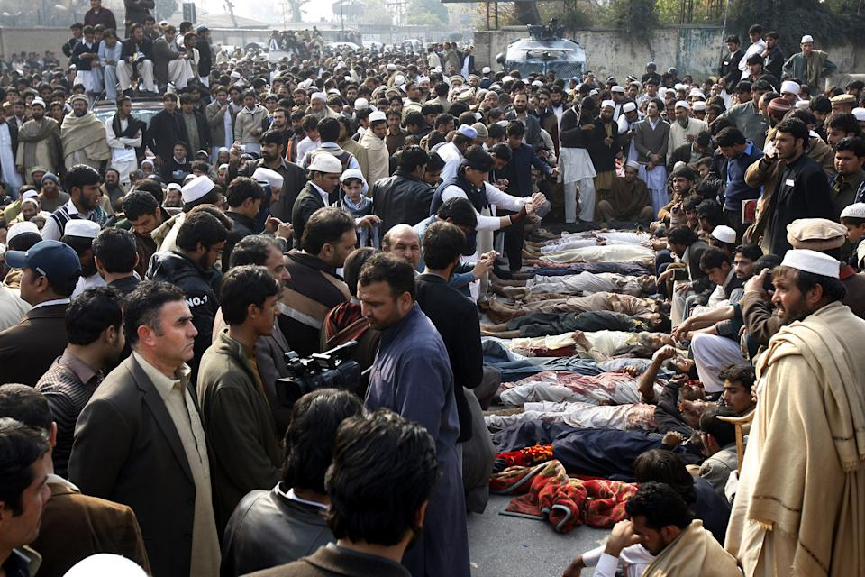Pakistani villagers gather around dead bodies in Peshawar, Pakistan, Wednesday, Jan. 16, 2013. Hundreds of villagers from northwest Pakistan protested Wednesday the killing of 18 of their relatives in an overnight raid that they blamed on security forces, displaying the bodies of the victims in the provincial capital. (AP Photo/Mohammad Sajjad)