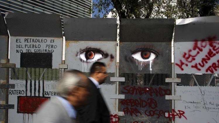 Pedestrians walk past fences with graffiti against the energy reform outside the Senate building in Mexico City