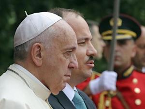 Pope Francis stands next to Albania's President Bujar Nishani upon arrival in Tirana