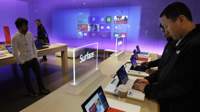 "FILE - In this Wednesday, Oct. 31, 2012, file photo, visitors try out Microsoft Corp.'s ""Surface"" touchscreen tablet computers, at ""Build,"" Microsoft Corp.'s developers conference, in Redmond, Wash. The Surface is Microsoft's first attempt at a general-purpose computer. In the past, it made the software and left it to other companies to make the machines. But to catch the tablet wave led by Apple's iPad, Microsoft felt it needed to make its own device.  (AP Photo/Ted S. Warren, File)"