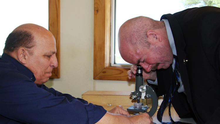 In this April 23, 2012, photo, Houston-area attorney Joe Gutheinz, right, looks through a microscope at rock particles that Rafael Navarro, left, a former Colombian toy manufacturer, contends are pieces of moon rock in Buffalo, Texas.  Navarro has placed the rock fragments on eBay and is offering them for sale for $300,000.  Gutheinz, a former investigator for NASA who practices law outside Houston, hunts for moon rocks, now-missing samples collected by the dozen American astronauts who walked on the lunar surface between 1969 and 1972. (AP Photo/Michael Graczyk)