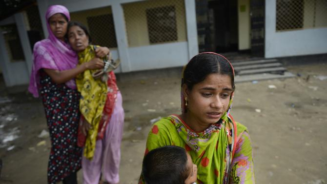 A Bangladeshi woman holds the child of her dead sister, as another pair mourn for their dead sister, both victims of a building collapse, at a makeshift morgue in Savar near Dhaka, Bangladesh, Wednesday May 8, 2013. Dozens of bodies recovered Wednesday from the building were so decomposed they were being sent to a lab for DNA identification, police said, as the death toll from Bangladesh's worst industrial disaster topped 800. (AP Photo/Ismail Ferdous)